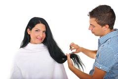 Hairstylist que corta o cabelo longo da mulher Imagens de Stock Royalty Free