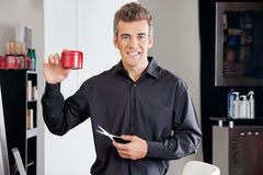 Hairstylist With Scissors Presenting Hairgel. Portrait of happy male hairstylist with scissors presenting hairgel bottle at salon Royalty Free Stock Photo