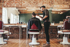 Hairstylist serving client at barber shop stock photo