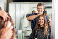 Hairstylist Setting Client's Hair While Looking At. Happy hairstylist setting up client's hair while looking at mirror in salon stock photography