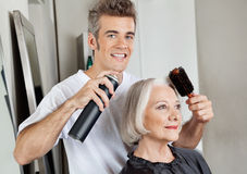 Hairstylist Setting Up Customer's Hair. Portrait of hairstylist setting up female customer's hair in parlor stock photos