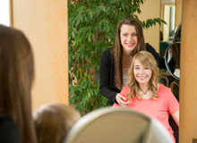 Hairstylist shows client her new haircut Royalty Free Stock Photos