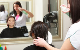 Hairstylist spraying hair woman client in hairdressing beauty salon Royalty Free Stock Images