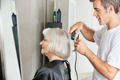 Hairstylist Straightening Customer's Hair Royalty Free Stock Images