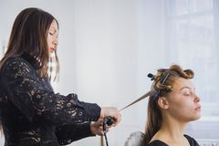 Hairstylist straightening the long brown hair Royalty Free Stock Images