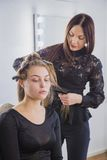 Hairstylist straightening the long brown hair. Of a female client using a heated hair straightener Royalty Free Stock Photography