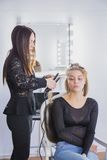Hairstylist straightening the long brown hair. Of a female client using a heated hair straightener Royalty Free Stock Images