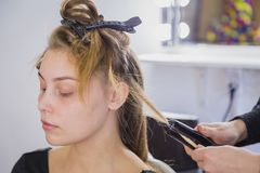 Hairstylist straightening the long brown hair. Of a female client using a heated hair straightener Stock Images