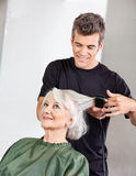 Hairstylist Straightening Senior Woman's Hair Stock Image