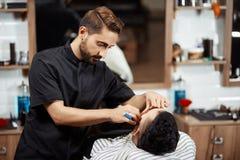 Hairstylist tnący chleb klient w nowożytnym fryzjerze męskim zdjęcie stock
