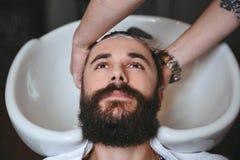 Hairstylist washing head of man with beard in barbershop Stock Photo