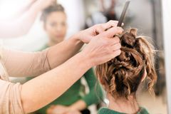 Hairstylist working on womans hairdo in close-up. Hairstylist working on creative hairdo, female visitor viewed from the back of her head in close-up with stock images