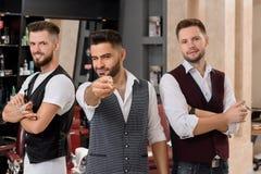 Hairstylists pozować, brodaty fryzjer męski wskazuje z nożycami przy kamerą i mrugać, zdjęcia royalty free