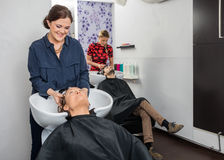Hairstylists Washing Customers Hair At Salon Royalty Free Stock Photos