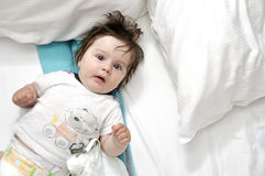 Hairy baby in bed with two pillows Royalty Free Stock Photos