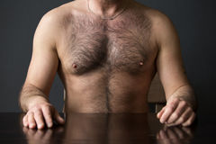 Hairy chest of man sitting at table Royalty Free Stock Photos