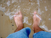 Hairy, Cold, Wet Feet. The ocean is washing ashore on my piggie toes Stock Images