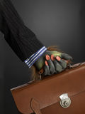 Hairy hand holding briefcase. Hairy hand holding holding briefcase against gray background Stock Photography