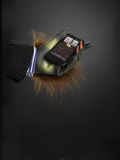 Hairy hand holding cell phone. Against gray background Royalty Free Stock Images