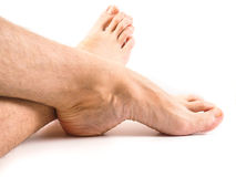 Hairy legs and feet of male person resting one white. Hairy legs and feet of male person resting towards white background Royalty Free Stock Images