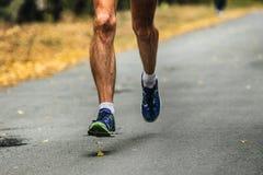 Hairy legs male runner. Running on asphalt road in autumn forest Stock Photo
