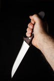Hand holding a knife. Hairy male hand  holding a knife over a black background Royalty Free Stock Images