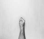 Hairy male hand showing gesture fig on gray background top view, black and white photo Royalty Free Stock Images