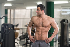 Hairy Muscular Man Flexing Muscles In Gym Stock Photo