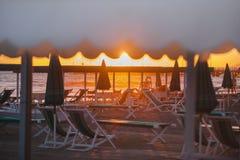 Sunset and beach near sea. Haise longues and umbrellas on the sunny evening beach Stock Photo