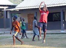 Haitańscy dziecko w wieku szkolnym bawić się sandlot piłkę nożną Zdjęcia Stock