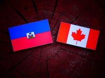 Haitańska flaga z kanadyjczyk flaga na drzewnym fiszorku odizolowywającym zdjęcie stock