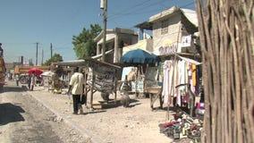 Haiti earthquake - camera car - sellers of wood and food stock video footage