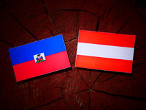 Haiti flag with Austrian flag on a tree stump stock images