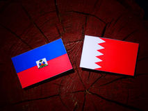 Haiti flag with Bahraini flag on a tree stump stock photo