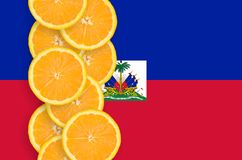 Haiti flag and citrus fruit slices vertical row. Haiti flag and vertical row of orange citrus fruit slices. Concept of growing as well as import and export of royalty free stock photo