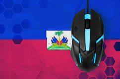 Haiti flag and computer mouse. Concept of country representing e-sports team. Haiti flag and modern backlit computer mouse. Concept of country representing e stock image