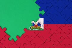 Haiti flag is depicted on a completed jigsaw puzzle with free green copy space on the left side.  vector illustration