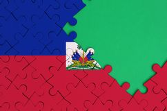 Haiti flag is depicted on a completed jigsaw puzzle with free green copy space on the right side.  stock illustration