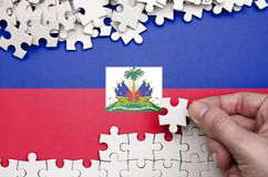 Haiti flag is depicted on a table on which the human hand folds a puzzle of white color.  stock photos