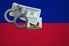 Haiti flag with handcuffs and a bundle of dollars. The concept of breaking the law and thieves crimes.  royalty free stock photo