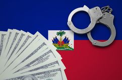 Haiti flag with handcuffs and a bundle of dollars. The concept of illegal banking operations in US currency.  stock photography
