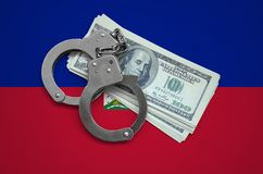 Haiti flag with handcuffs and a bundle of dollars. Currency corruption in the country. Financial crimes.  royalty free stock photography