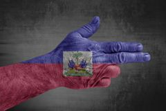 Haiti flag painted on male hand like a gun. On concrete background stock photography