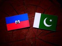 Haiti flag with Pakistan flag on a tree stump isolated. Haiti flag with Pakistan flag on a tree stump stock photo