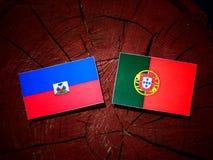 Haiti flag with Portuguese flag on a tree stump isolated. Haiti flag with Portuguese flag on a tree stump stock images