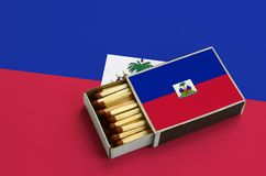 Haiti flag is shown in an open matchbox, which is filled with matches and lies on a large flag.  stock images