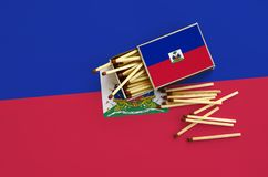 Haiti flag is shown on an open matchbox, from which several matches fall and lies on a large flag.  royalty free stock photography