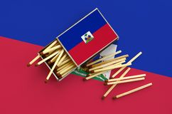 Haiti flag is shown on an open matchbox, from which several matches fall and lies on a large flag.  stock photo