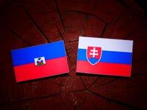 Haiti flag with Slovakian flag on a tree stump isolated. Haiti flag with Slovakian flag on a tree stump stock photography
