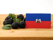 Haiti flag on a wooden panel with blackberries isolated on a whi. Te background royalty free stock photography